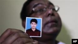 17일 폭탄 테러 혐의로 체포된 콰지 나피스의 사진을 들고있는 그의 아버지 콰지 아사눌라 씨.