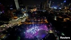 Peserta pawai tahunan Pink Dot, yang diorganisasi oleh komunitas LGBT Singapura, membentuk formasi bertuliskan cabut Undang-Undang 377A yang mengkriminalisasi kaum gay, di Hong Lim Park, Singapura, 29 Juni 2019. (Foto: Reuters)