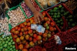 Seorang penjual sayur menerima uang dari pembeli di sebuah pasar tradisional di Jakarta, 2 Mei 2019. (Foto: Reuters)