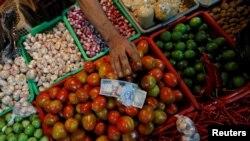 Seorang penjual sayuran menerima uang dari pembeli di sebuah pasar tradisional di Jakarta, 2 Mei 2019. (Foto: Reuters)