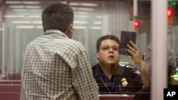 FILE - A Customs and Border Protection officer checks the passport of a non-resident visitor to the United States at McCarran International Airport, Dec. 13, 2011, in Las Vegas.