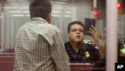 Nhân viên Hải quan Hoa Kỳ kiểm tra hộ chiếu của hành khách.