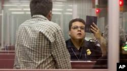 一名美國海關邊防人員檢查進入美國機場人士的護照。(資料圖片)