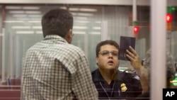 在内华达州拉斯韦加斯的麦卡伦国际机场内,一名美国海关与边防检查官正在检查一名赴美游客的护照。(2011年12月13日资料图)