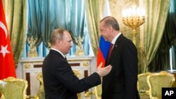 FILE - Russian President Vladimir Putin, left, speaks to Turkey's President Recep Tayyip Erdogan during their meeting in the Kremlin in Moscow, Russia, March 10, 2017.