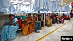 FILE - Employees sit during their lunch time inside a textile mill in India.