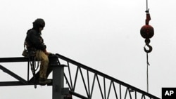 A worker sits atop some ironwork at the construction site of a new store at the Harvard Park Shopping Center in Warrensville Hts., December 7, 2011