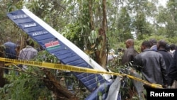 People gather at the scene where a police helicopter crashed at a forest in the Kibiko area of Ngong township, on the outskirts Nairobi, June 10, 2012.