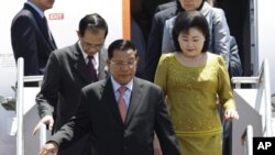 Cambodian Prime Minister Hun Sen, center, and his wife Bun Rany alights from a plane as they arrive at the Ngurah Rai airport in Bali, Indonesia on Wednesday Nov. 16, 2011. Hun Sen is here to attend the 19th ASEAN Summit and East Asia Summit.