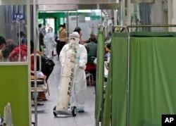 Seorang paramedis mendorong tangki oksigen di ruang gawat darurat sebuah rumah sakit yang penuh sesak di tengah kasus COVID-19, di Surabaya, Jawa Timur, Jumat, 9 Juli 2021. (AP)