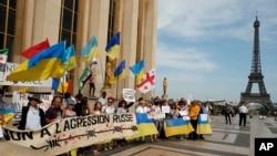"""Para demonstran memegang sebagian besar bendera nasional Ukraina dan sebuah spanduk bertuliskan """"Tidak untuk agresi Rusia"""" dalam sebuah aksi unjuk rasa di dekat Menara Eiffel di Paris, Prancis, 28 Mei 2017, menentang kunjungan Presiden Rusia Vladimir Putin ke Perancis."""