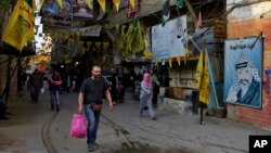 People walk underneath the banners of Fatah and the Palestinian flags inside the Bourj al-Barajneh Palestinian refugee camp in Beirut, Lebanon, May 4, 2017.