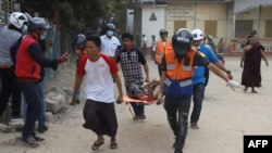 A wounded man is carried on a stretcher by a medical team after security forces opened fire on protesters during a demonstration against the military coup in Mandalay on February 20, 2021. (Photo by str / AFP)