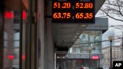 People walk past a display with currency exchange rates in central of Moscow, Russia, Dec. 1, 2014.