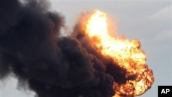 A fuel storage depot, burns after being struck during fighting between rebels and pro-Moammar Gadhafi forces, in Sedra, eastern Libya, March 9, 2011.