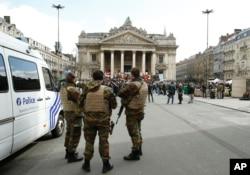 Tentara Belgia berjaga-jaga di samping tempat untuk mengenang korban serangan Brussels baru-baru ini, di Place de la Bourse di Brussels, 27 Maret 2016.