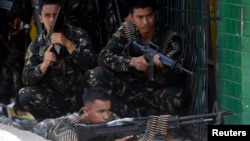 Government soldiers battling Moro National Liberation Front rebels take up positions in downtown Zamboanga city, in southern Philippines, Sept. 11, 2013.