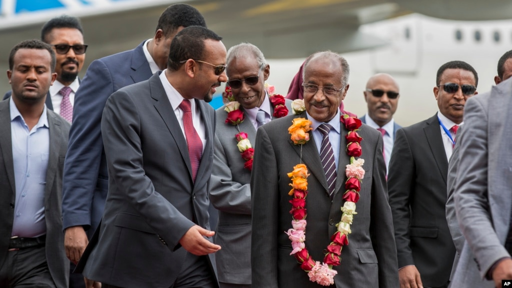 Eritrea's foreign minister, Osman Saleh Mohammed, center right, is welcomed by Ethiopia's prime minister, Abiy Ahmed, center left, upon the Eritrean delegation's arrival at the airport in Addis Ababa, Ethiopia, June 26, 2018.