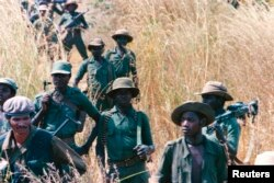 FILE - UNITA troops walk through a field, 20 miles from the front line, at Munhango, Angola, April 29, 1986. The UNITA forces, led by Jonas Savimbi, were engaged in a guerilla war against the Angola government.