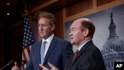 Sen. Jeff Flake, R-Ariz., left, and Sen. Chris Coons, D-Del., talk to reporters after making speeches on the Senate floor calling for a resolution to back the U.S. intelligence community findings that Russia interfered in the 2016 election and calling for other responses to the meddling, on Capitol Hill in Washington, July 19, 2018.