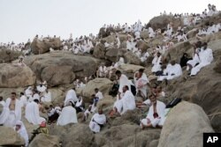 FILE - Muslim pilgrims gather to pray at Jabal al-Rahma holy mountain, or the mountain of forgiveness, during the annual pilgrimage, near Mecca, Saudi Arabia, Oct. 3, 2014.