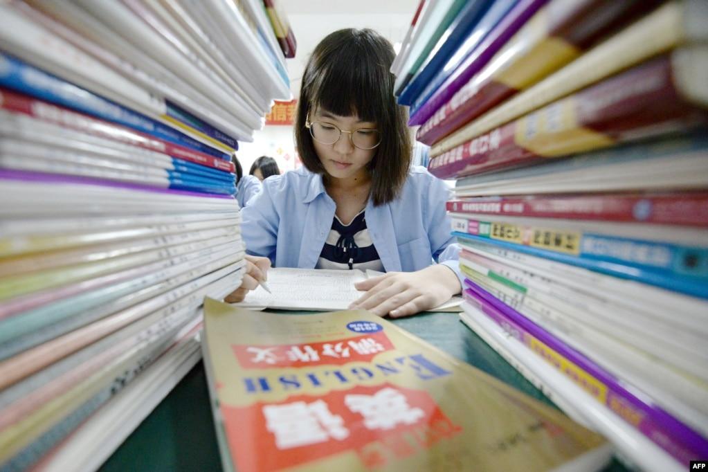 """2018年5月23日,中國河北省邯鄲一名高中生在""""高考""""前在高高的資料堆中復習功課。 中國的高考將於今年6月7日和6月8日舉行。 考生壓力山大,複習資料也堆如小山。"""