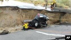 En esta imagen, proporcionada por el Departamento de Bomberos del Condado Riverside, equipos de emergencia trabajan después de que una camioneta quedara atrapada en el derrumbe de un tramo elevado de la Interestatal 10, el domingo 19 de julio de 2015, en Desert Center, California.