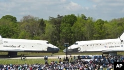 Space shuttles Enterprise (l) and Discovery meet nose-to-nose at the beginning of a transfer ceremony at the Smithsonian's Steven F. Udvar-Hazy Center in Chantilly, Virginia, April 19, 2012.