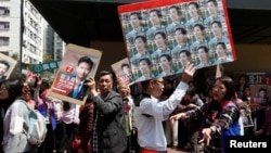 A supporter carrying photos of pro-democracy candidate Edward Yu walks past a supporter of Vincent Cheng from Democratic Alliance for the Betterment and Progress of Hong Kong, March 11, 2018.
