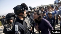 A young Jewish settler, right, speaks with an Israeli police officer near buildings slated for demolition by order of Israel's high court, in the West Bank Jewish settlement of Beit El near Ramallah, July 28, 2015.