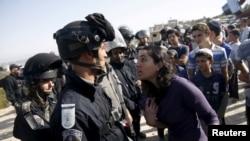 Seorang pemukim Yahudi (kanan) berbicara dengan seorang polisi Israel dekat gedung yang akan dihancurkan di permukiman Beit El di Tepi Barat dekat Ramallah (28/7).