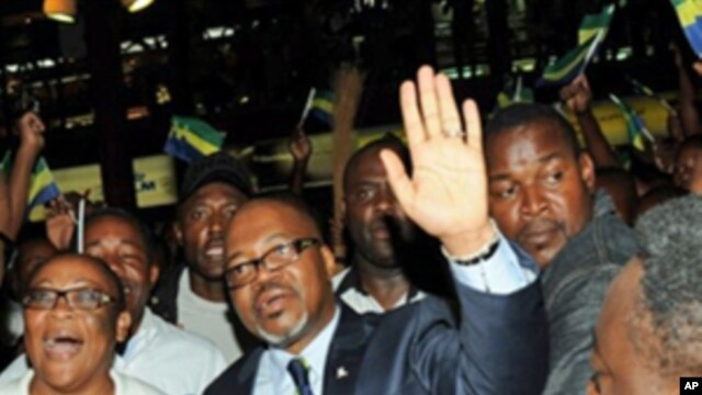 Andre Mba Obame (C) (AMO) greets supporters upon his arrival at the airport Leon Mba in Libreville, 30 Dec 2010