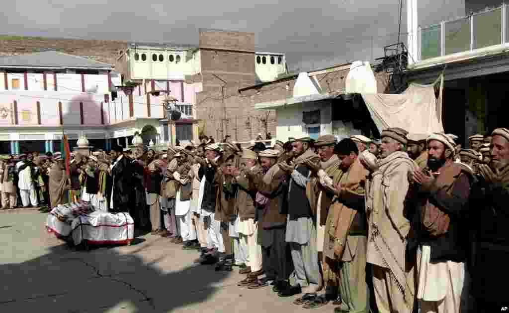 Para kerabat dan simpatisan berdoa dekat jenazah petugas vaksin polio yang tewas dalam ledakan bom di Parachinar, Pakistan (31/1). (AP/Dilawar Hussain)