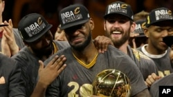ກອງໜ້າທີມ Cleveland Cavaliers ທ້າວ LeBron James, ກາງ, ສະເຫຼີມສະຫຼອງກັບສະມາຊິກຂອງທີມ ຫຼັງຈາກ ຍາດໄດ້ໄຊຊະນະ ຈາກທີມ Golden State Warriors ໃນເກມທີ 7 ຂອງຮອບສຸດທ້າຍຂອງສະມາຄົມ NBA ໃນນະຄອນ Oakland ຂອງລັດ California, ວັນອາທິດ ທີ 19 ມິຖຸນາ 2016.