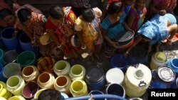 Residents get their containers filled with drinking water from a municipal water tanker at a slum in Kolkata.