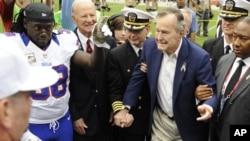 Mantan Presiden AS George H.W. Bush dipapah saat menghadiri sebuah pertandingan sepakbola di Houston, Texas (4/11). (AP/Dave Einsel)