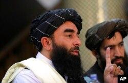 Juru bicara Taliban Zabihullah Mujahid, kiri, berbicara pada konferensi pers pertamanya di Pusat Informasi Media Pemerintah, di Kabul, Afghanistan, Selasa, 17 Agustus 2021. (Foto: AP)