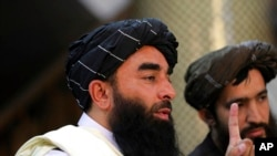 Taliban spokesman Zabihullah Mujahid, left, speaks at his first news conference at the Government Media Information Center, in Kabul, Afghanistan, Tuesday, Aug. 17, 2021.