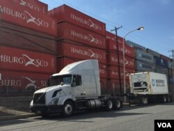 Cargo containers line the Delaware River as a truck sits idly by the roadside, in Philadelphia, June 2016. (A. Pande / VOA)