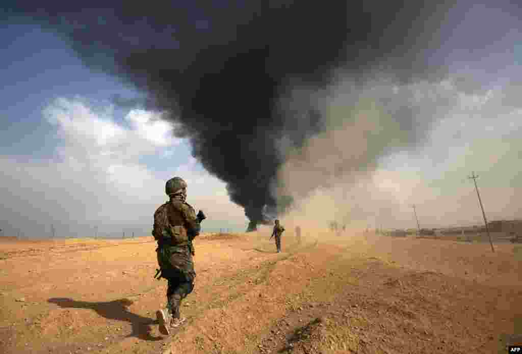 Iraqi forces and members of the Hashed al-Shaabi (Popular Mobilization units) advance towards the city of al-Qaim, in Iraq's western Anbar province near the Syrian border as they fight against remnant pockets of Islamic State group jihadists.