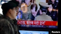 12月13日首尔火车站:韩国士兵走过电视上金正恩处决张成泽的报道镜头