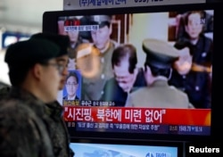 FILE - South Korean soldiers walk past a television showing reports on the execution of Jang Song Thaek, who is North Korean leader Kim Jong Un's uncle, at a railway station in Seoul, Dec. 13, 2013.