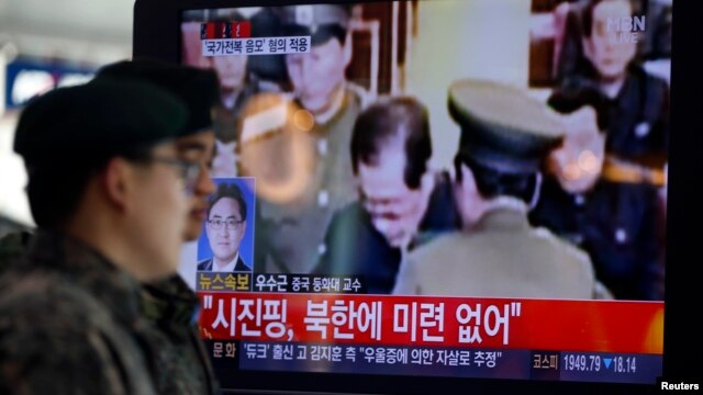 South Korean soldiers walk past a television showing reports on the execution of Jang Song Thaek, who is North Korean leader Kim Jong Un's uncle, at a railway station in Seoul on December 13, 2013.