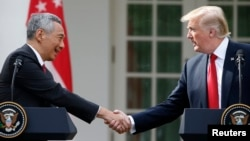 Singapore's Prime Minister Lee Hsien Loong and U.S. President Donald Trump shake hands before giving joint statements in the Rose Garden of the White House in Washington, Oct. 23, 2017.