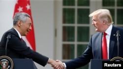 នាយករដ្ឋមន្រ្តីសិង្ហបុរី Lee Hsien Loong និងប្រធានាធិបតីសហរដ្ឋអាមេរិក Donald Trump ចាប់ដៃជាមួយគ្នាមុននឹងផ្តល់សេចក្តីថ្លែងរួមនៅក្នុងសួនកុឡាបក្នុងសេតវិមានរដ្ឋធានីវ៉ាស៊ីនតោនកាលពីថ្ងៃទី២៣ តុលា ២០១៧។