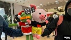 有示威者帶連豬及PEPE公仔參與尖沙咀海港城平安夜和你Sing抗爭行動,繼續爭取五大訴求、缺一不可。(美國之音湯惠芸)