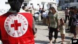 지난 2012년 8월 홍수 피해를 입은 평안남도 안주에서 북한 적십자 요원들이 구호물자를 나눠주고 있다. (자료사진)