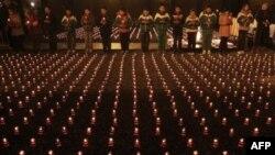 Sinh viên Trung Quốc thắp nến cầu nguyện cho các nạn nhân vụ thảm sát Nam Kinh gần đài tưởng niệm để đánh dấu kỷ niệm lần thứ 74 tại Viện Bảo tàng Thảm sát Nam Kinh, phía đông Trung Quốc, ngày 12/12/2011