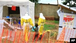 FILE - Health workers walk with a boy suspected of having contracted the Ebola virus, at an Ebola treatment center in Beni, DRC, Sept 9, 2018.