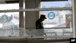 """A military officer inspects a bus stop damaged in Wednesday's suicide bombings in Jakarta, Indonesia, May 25, 2017. Indonesia's President Joko """"Jokowi"""" Widodo ordered a thorough investigation of the network behind two suicide bombings that targeted police."""